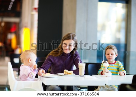 Young mother with two kids enjoying meal sitting at cafe - stock photo