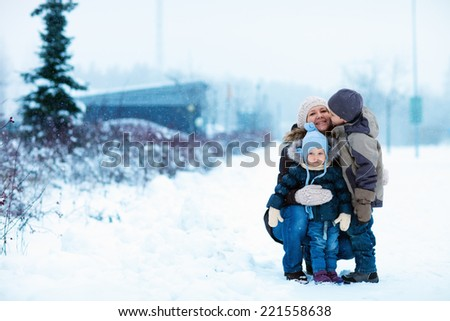 Young mother with two kids outdoors on beautiful winter day with snow - stock photo