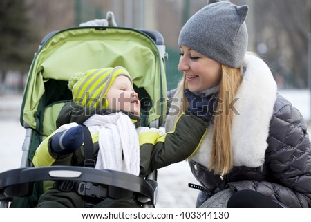 Young mother with two year old son in winter park
