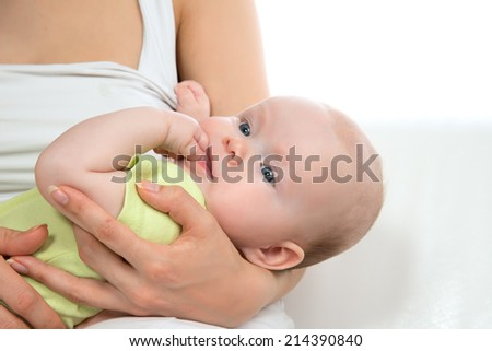 Young mother woman holding infant child baby girl lying on her hands on a whine background - stock photo