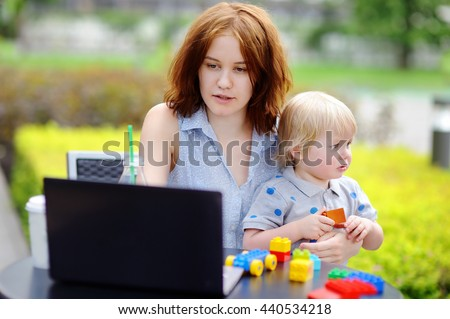 Young mother working oh her laptop and holding her sad toddler son - stock photo