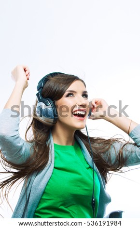 Young motion woman with headphones listening music .Music teenager girl dancing against isolated white background. Beautiful female model.