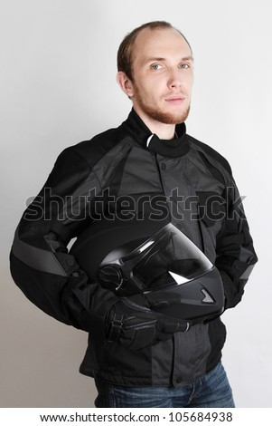 young motorcyclist man holding helmet in studio