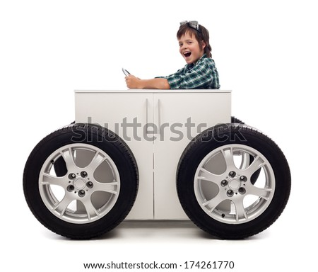 Young motorist - boy playing with car tires attached to wooden box - stock photo