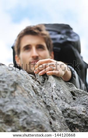 Young mountain climber scaling a cliff, focus on hand - stock photo