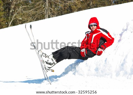 Young mountain-skier resting on the slope - stock photo