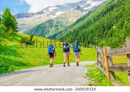 Young mountaineers on the background of alpine landscape, green slopes and high mountain peaks, Austria, Alps - stock photo