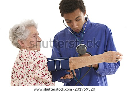 Young mulatto Doctor checking elderly woman's blood pressure  - stock photo