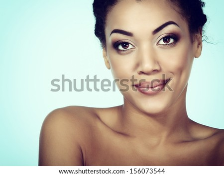 Young mulatto fresh woman with beautiful makeup looking at camera, isolated on blue, toned - stock photo