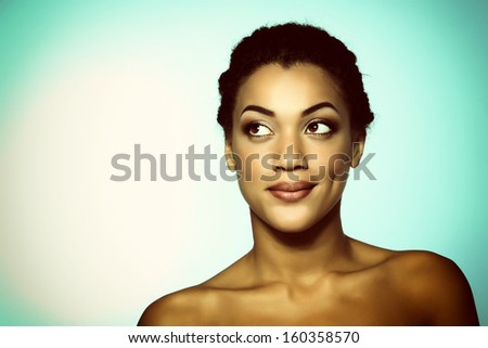 Young mulatto fresh woman with beautiful makeup looking up into the corner, isolated on blue, toned - stock photo