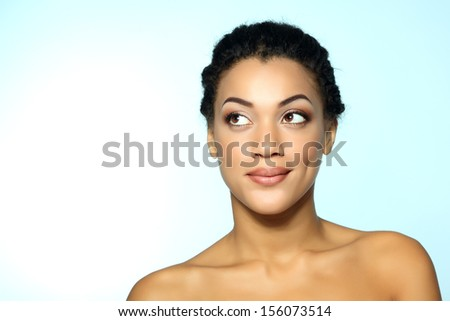Young mulatto fresh woman with beautiful makeup looking up into the corner, over blue - stock photo