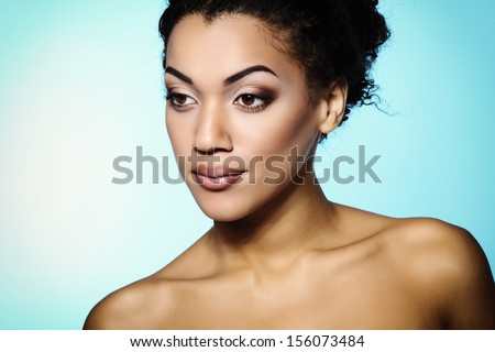 Young mulatto fresh woman with beautiful makeup, over blue - stock photo
