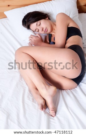 Young mult etnic woman lying and sleeping in bed