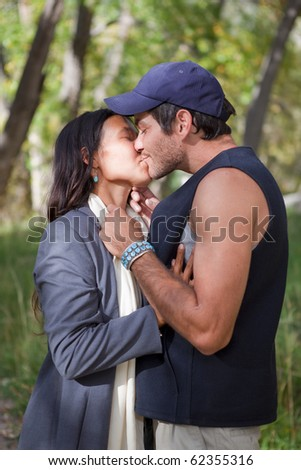 Young multi cultural couple kissing in fall forest - stock photo