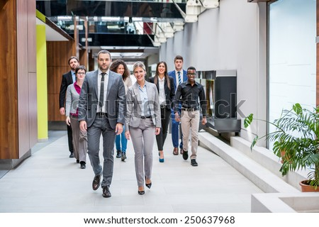 young multi ethnic business people group walking  - stock photo