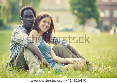young multi-ethnic couple having fun together at the park - stock photo