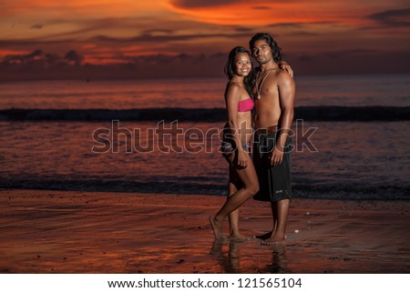 Young multi-ethnic couple on romantic beach at sunset in the tropics - stock photo