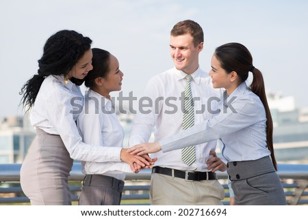 Young multicultural colleagues stacking their hands as a symbol of joined efforts - stock photo