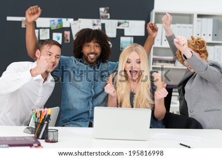 Young multiethnic business team cheering as they sit grouped around a laptop computer celebrating a success - stock photo