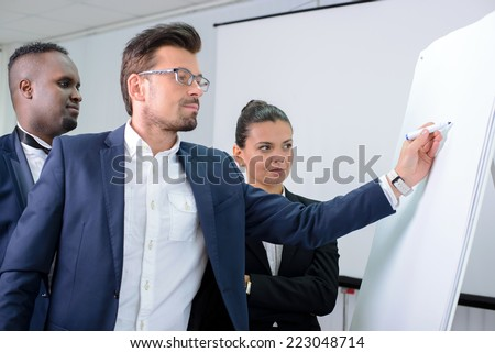Young multiethnic business team planning a new strategy standing grouped in front of a flip chart analyzing a chart