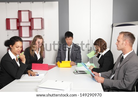 Young multiethnic business team with diverse men and women having a meeting around a conference table - stock photo