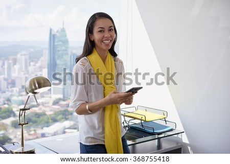Young multiethnic Chinese Hispanic woman leaning on table in a modern office building, with a beautiful sight of the city in background. She holds a mobile phone and smiles at camera - stock photo