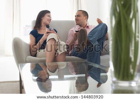 Young multiethnic couple drinking wine in living room at home - stock photo