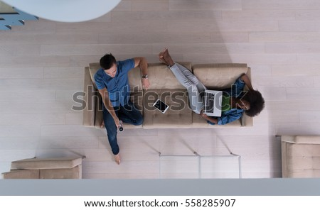 Young multiethnic couple relaxes on the sofa in the luxury living room, using a tablet and remote control top view