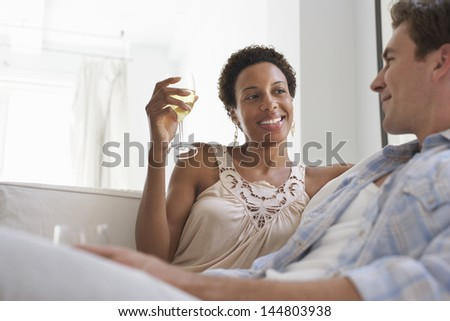 Young multiethnic couple with wine glasses in living room at home - stock photo