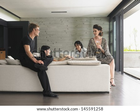 Young multiethnic people drinking champagne in villa living room - stock photo