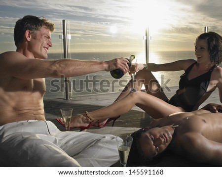 Young multiethnic people drinking champagne on pool deck near sea at sunset - stock photo