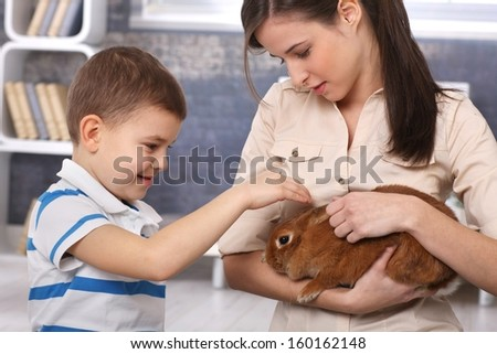 Young mum and happy little boy caressing cute brown pet rabbit at home.