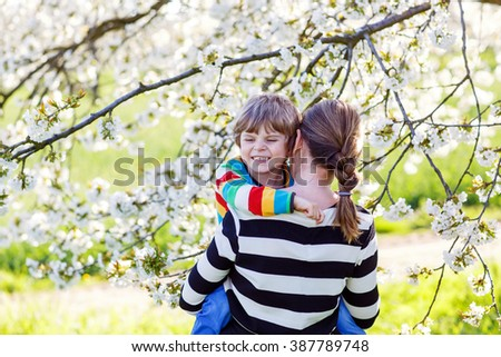 Young mum and her little son, blond child hugging in blooming cherry garden in spring. Happy family celebrating mother's day. - stock photo