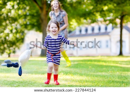 Young mum and her little toddler girl in yellow rubber boots having fun together, in summer park playing with rain drops toy - stock photo