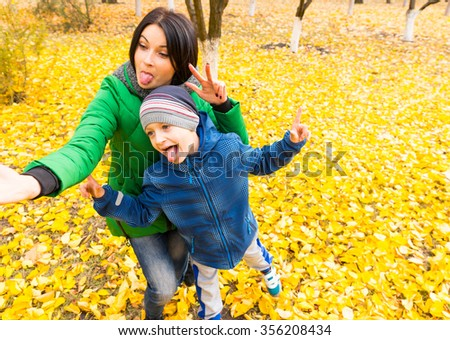 Young mum and her son goofing around as they pull comical faces while posing for a selfie in a colorful yellow autumn park - stock photo