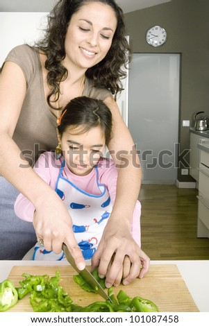 Young mum chopping vegetables with young daughter in a family home kitchen. - stock photo
