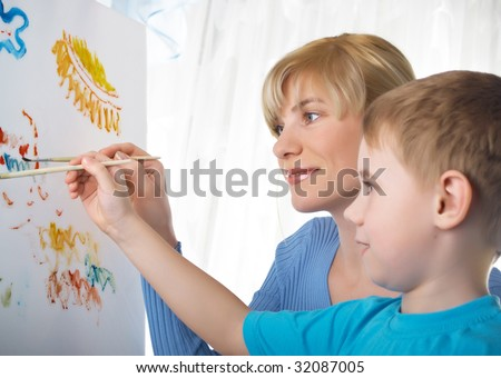 Young mum draws with the son paints