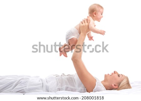 young mum holding small baby. beautiful blond lifting baby up and smiling