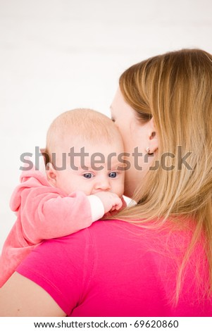 Young mum holds on hands of the chest baby - stock photo