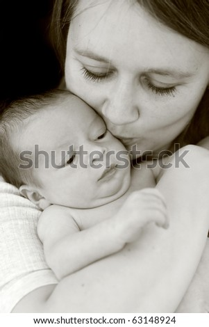 Young mum kissing her baby - stock photo