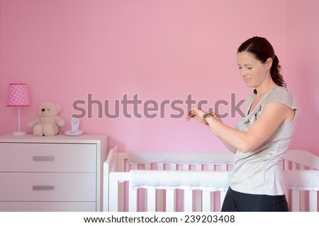 Young mum looking at her watch while her baby sleeps. Concept photo parenthood and motherhood. - stock photo