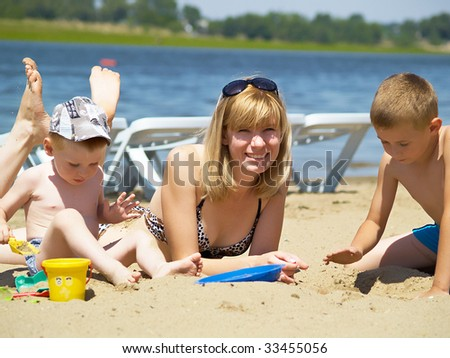 Young mum plays with two sons on the nature