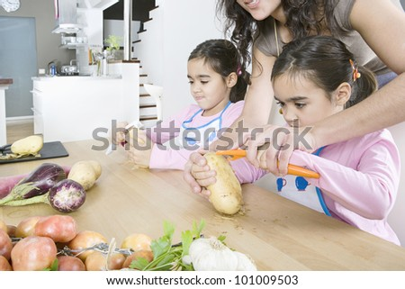 Young mum teaching twin daughters how to peel potatoes.