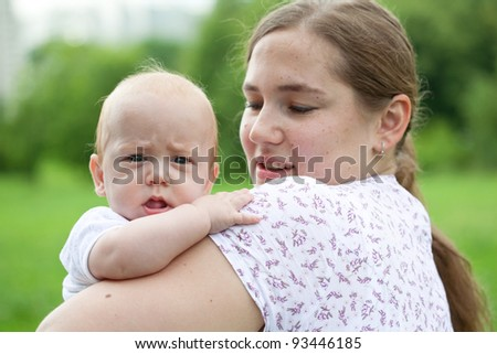 Young mum walks with the child in city park - stock photo