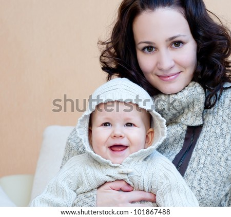 young mum with a small son in a room interior - stock photo