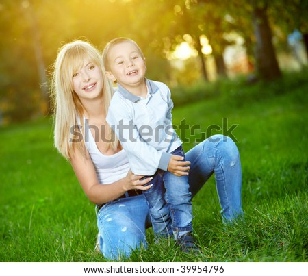 Young mum with the small son are amused in a summer garden