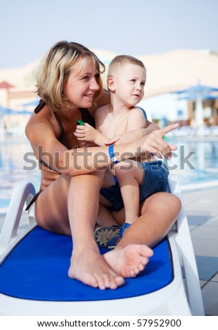 Young mum with the son sit on a chaise lounge, mum showing a finger aside - stock photo