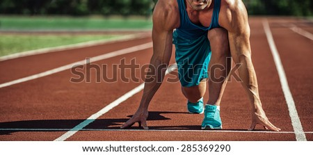 young muscular athlete is at the start - stock photo