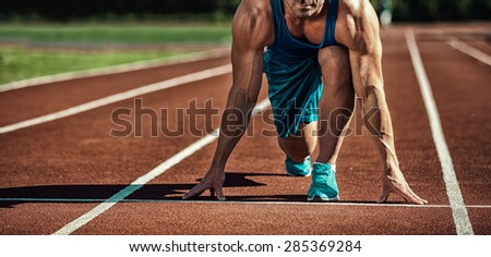 young muscular athlete is at the start of the treadmill - stock photo