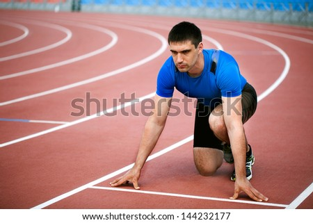 young muscular athlete is at the start of the treadmill at the stadium